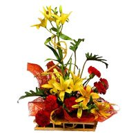 Rakhi and Yellow Lily 6 Red Carnation Flower Arrangement with Rakhi Delivery in India